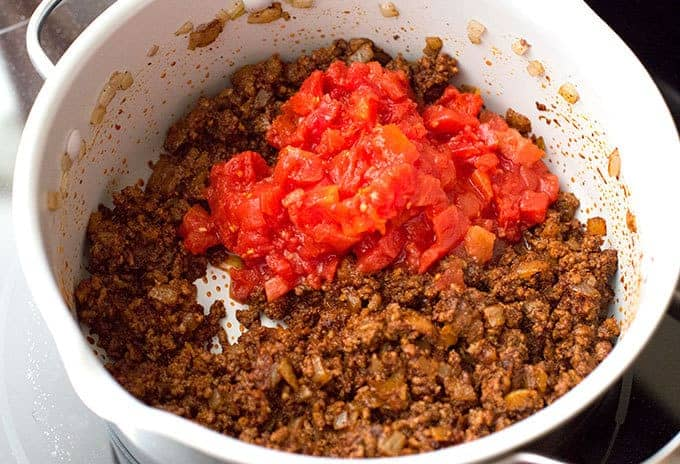 diced tomatoes over chili seasoned ground beef and onions in a soup pot