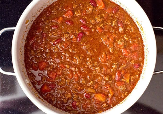 beans, beef broth, and tomato sauce added to chili seasoned beef, onions, and tomatoes in a pot