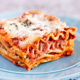 Slice of the best classic lasagna recipe with layers of pasta, homemade meat sauce, ricotta mozzarella and parmesan cheese
