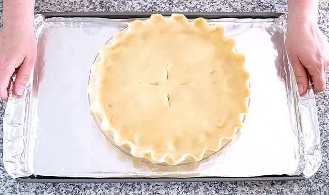 Unbaked chicken pot pie on a baking sheet