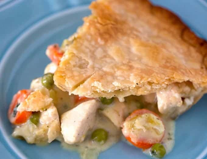 Slice of classic chicken pot pie with pie crust and creamy filling