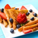 The best classic french toast recipe with pieces sliced on a plate with maple syrup, strawberries and blueberries