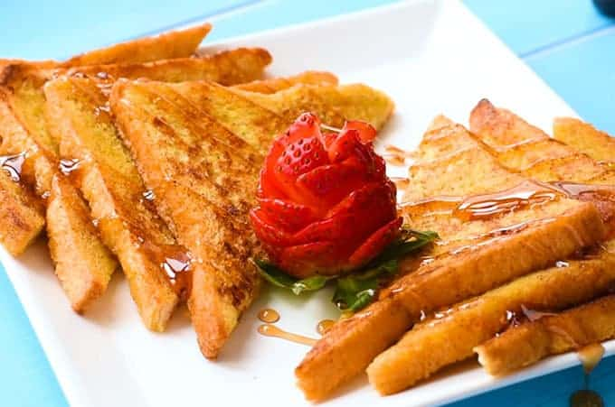 the best french toast sliced on a plate with a strawberry