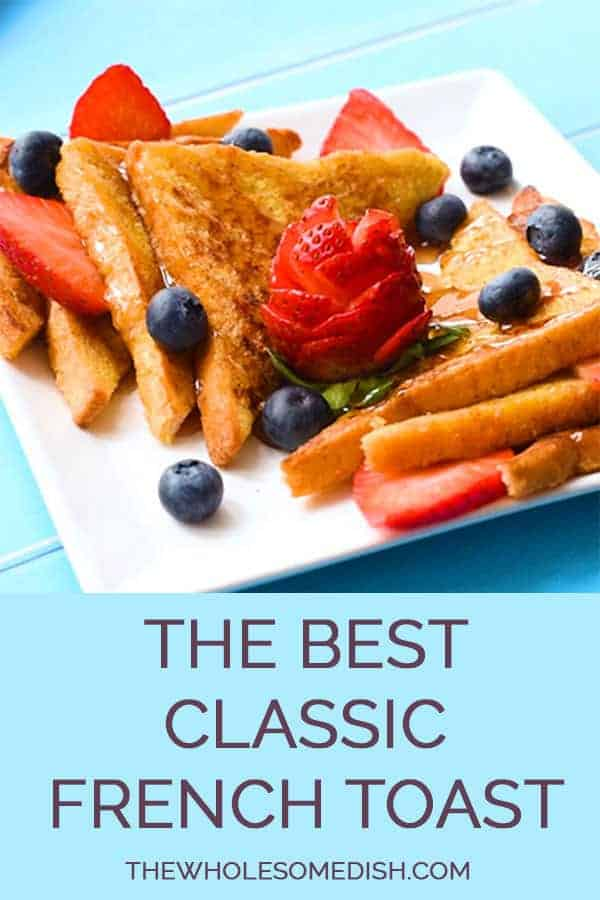 The Best Easy French Toast Recipe sliced on a plate with maple syrup, strawberries, and blueberries