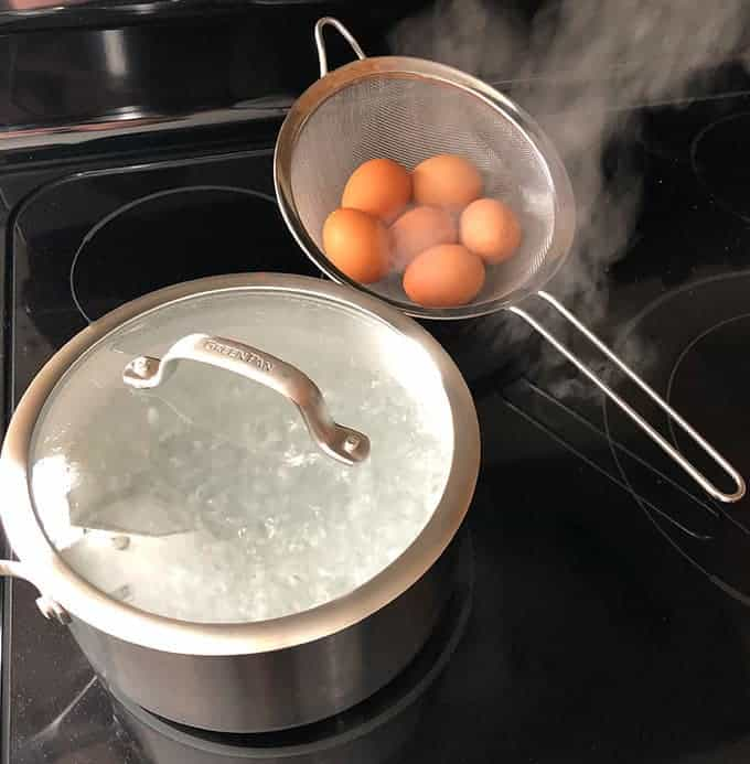 pot of boiling water and a mesh strainer filled with eggs to boil