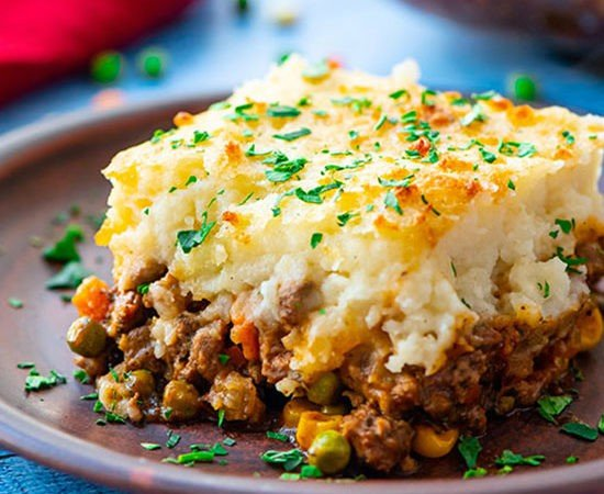 A piece of the best shepherd's pie on a plate with layers of cottage pie beef and vegetable gravy topped with parmesan cheese mashed potatoes