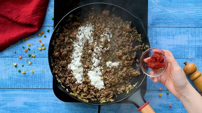 Adding flour and tomato paste to a skillet full of ground beef and onions for Easy Shepherd's Pie