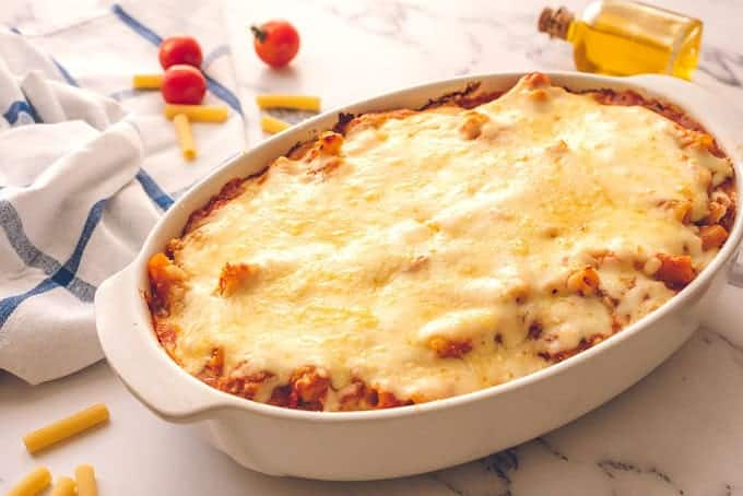 Large baking dish full of baked ziti covered in cheese