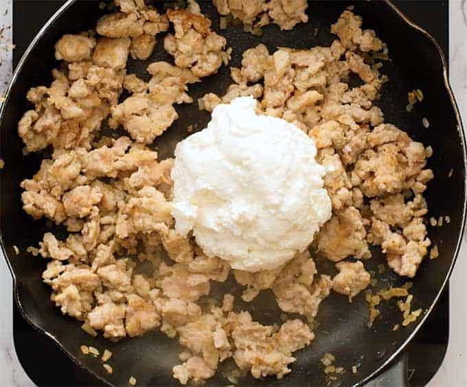 Skillet full of Italian sausage and ricotta cheese