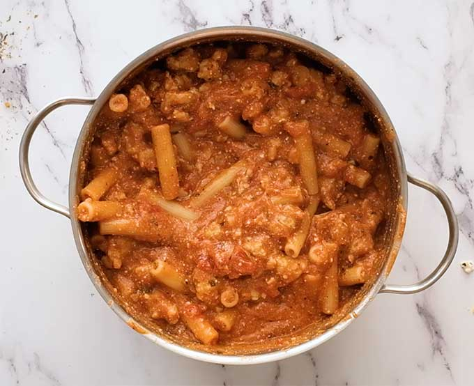 Large pot full of cooked ziti pasta in meat sauce
