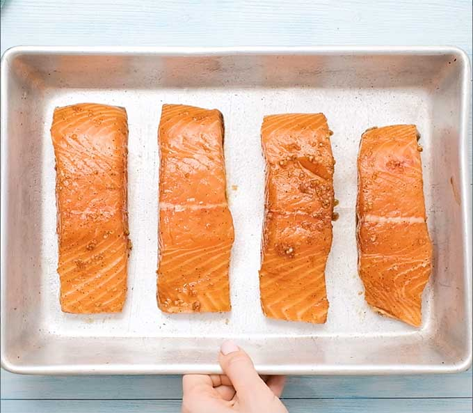 4 uncooked marinaded salmon fillets in a baking dish