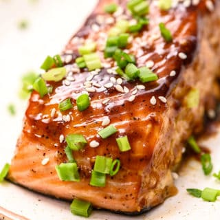 piece of baked salmon smothered in dark teriyaki glaze and sprinkled with sesame seeds and sliced green onions