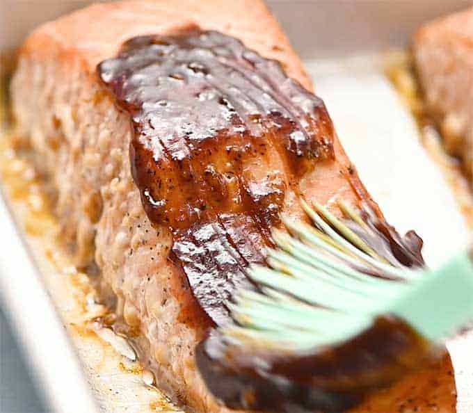 Baked salmon fillet being brushed with thick teriyaki glaze