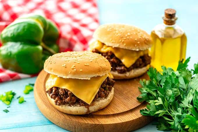 Two sloppy Joe sandwiches with cheese on a cutting board.