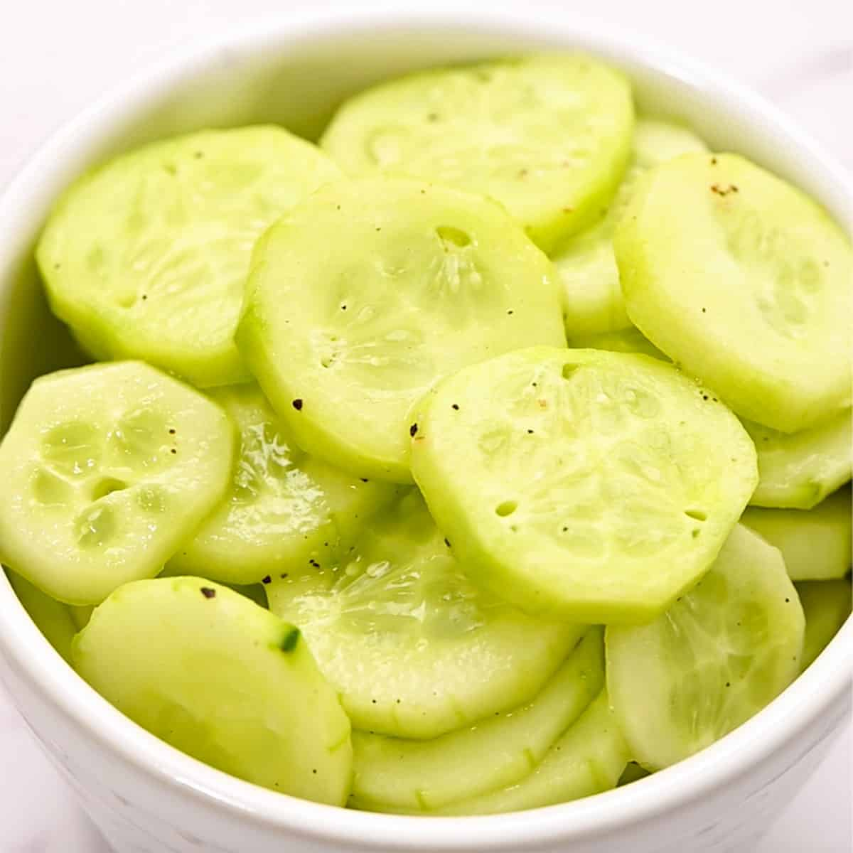white bowl full of peeled, sliced, marinated cucumbers