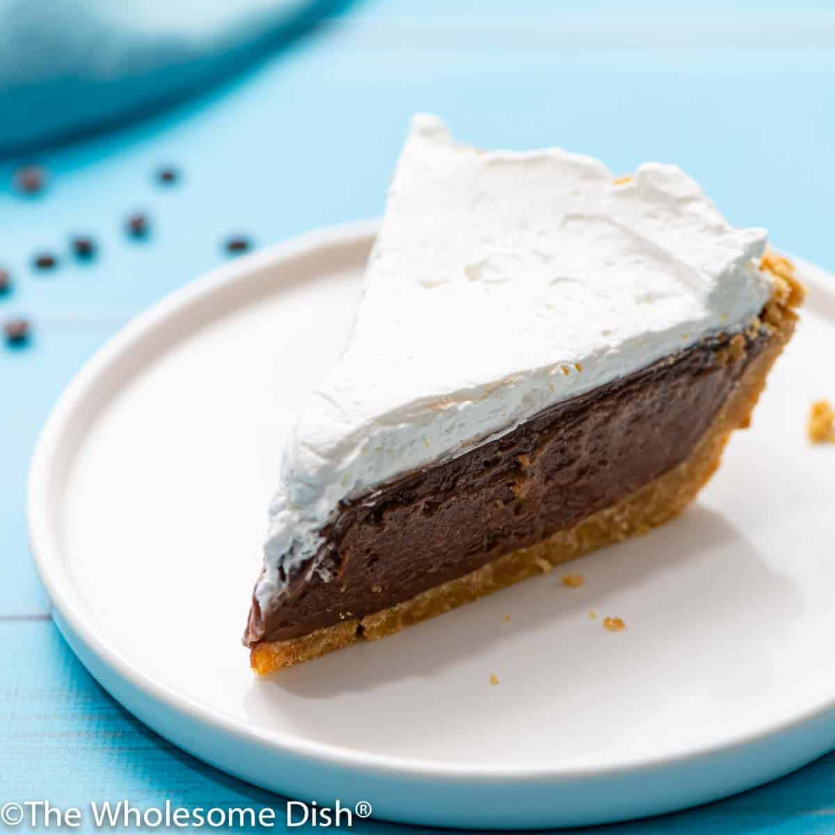 slice of chocolate cream pie with whipped cream on top on a white plate