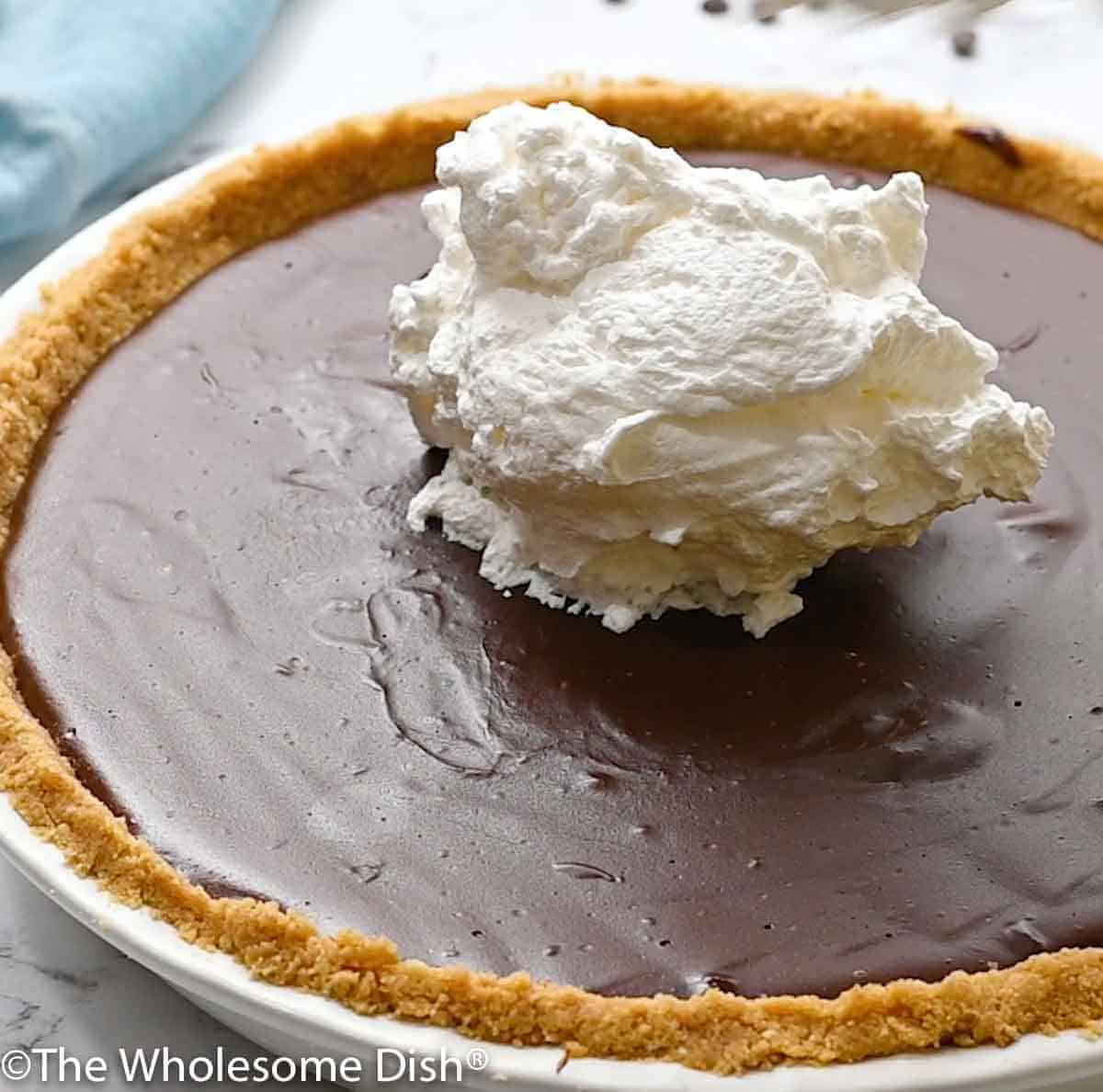 a dollop of whipped cream on top of a cold chocolate cream pie