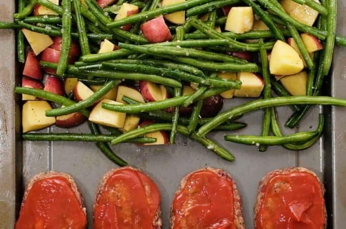 4 mini meatloafs topped with ketchup on a baking sheet with potatoes and green beans
