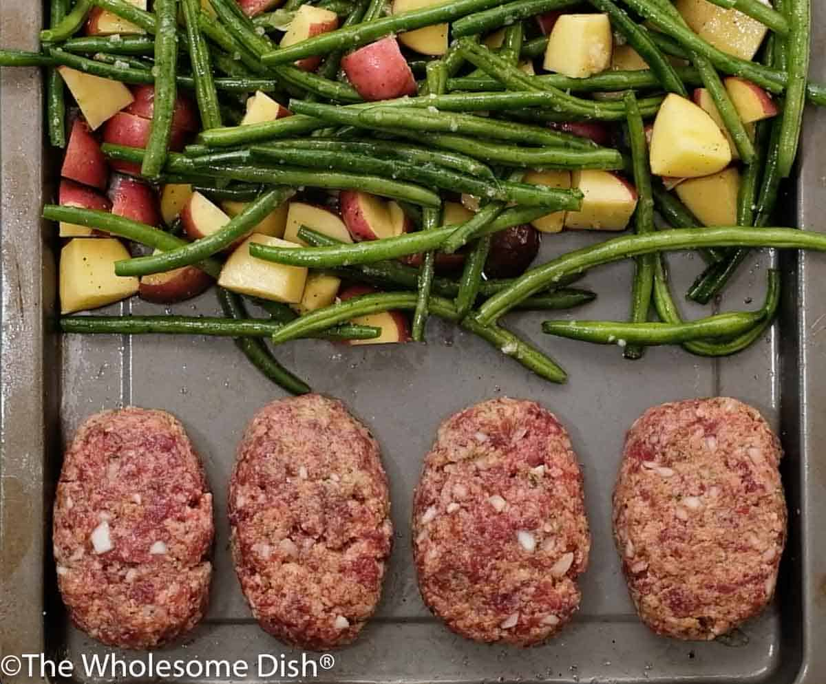 4 personal size meatloafs on a sheet pan with chopped potatoes and green beans ready to bake