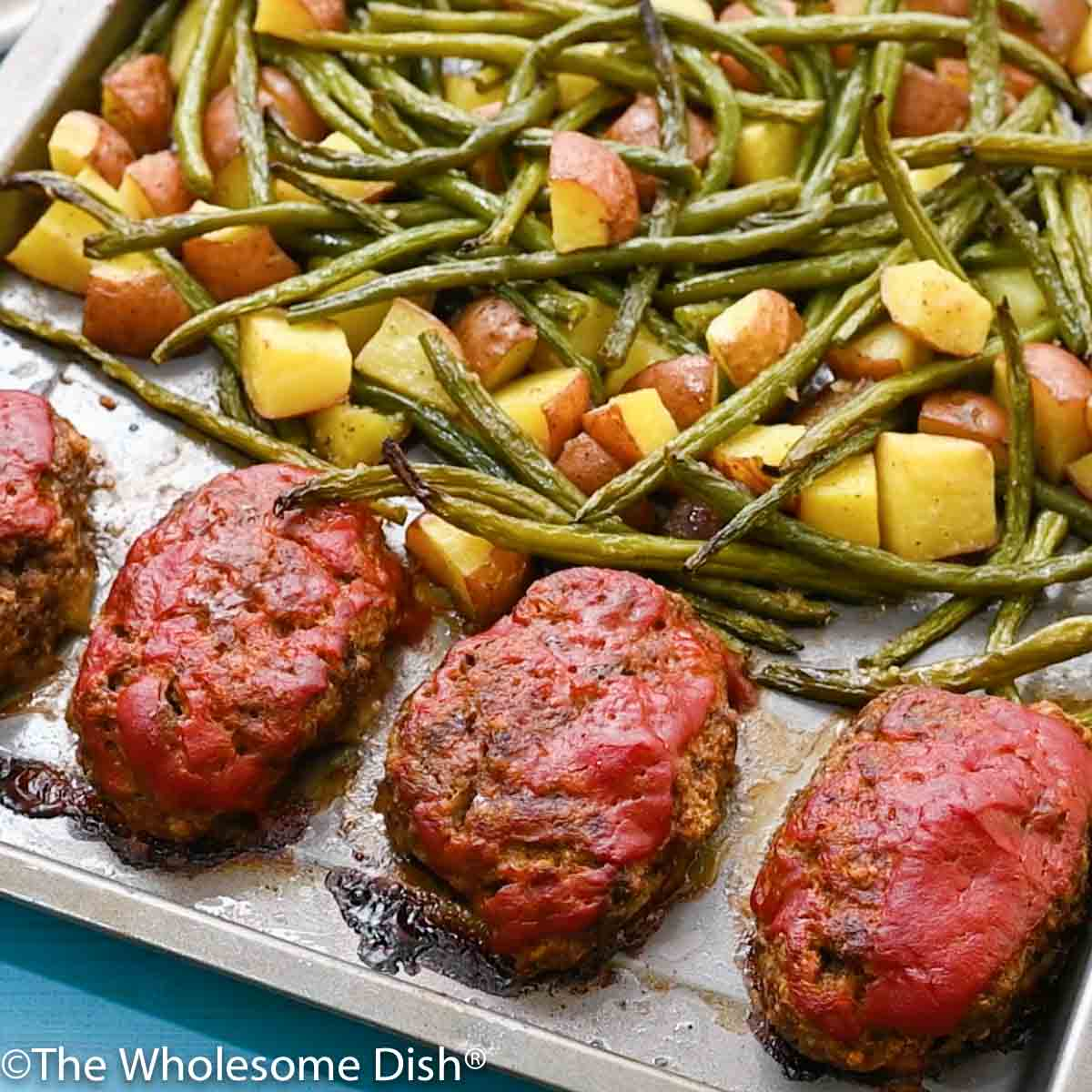 cooked meatloaf, potatoes, and green beans on a sheet pan
