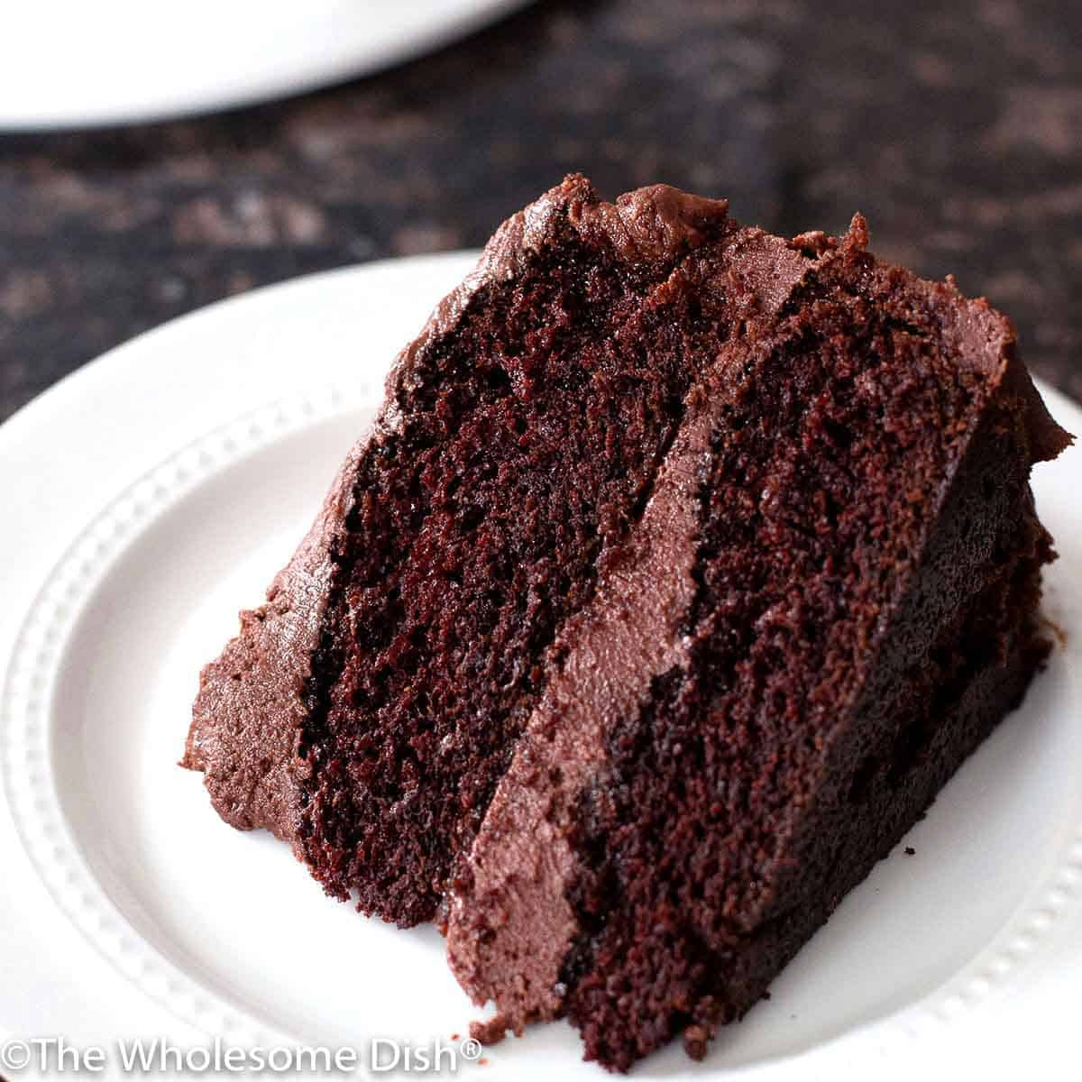 slice of homemade chocolate cake with chocolate frosting on a white plate