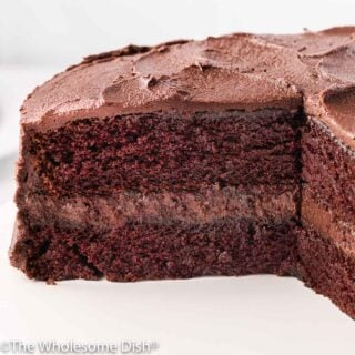 Chocolate layer cake with chocolate frosting with a large piece taken out